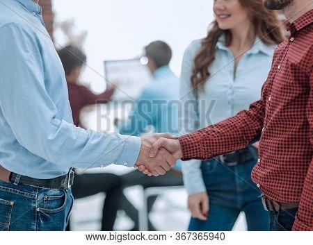 Business people handshake in modern office.