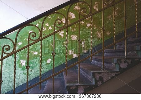 Classic Vintage Metal Baluster Against Aged Green Wall In Abandoned Historical Building In Lviv, Ukr