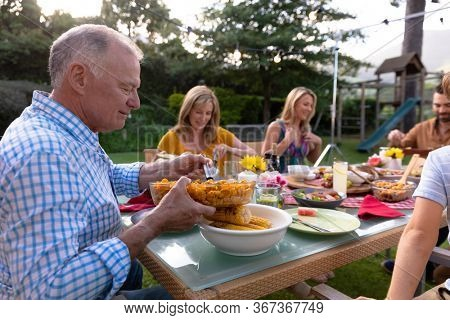 Side view close up of a senior Caucasian man sitting at a table serving food during a multi-generation family meal in the garden, his relatives serving food and eating in the background