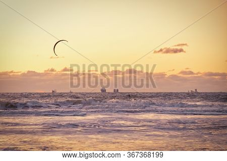 Extreme Sport Kitesurfing, Cargo Ships On The Horizon. Surfer In The Sea At Scheveningen At Sunset.