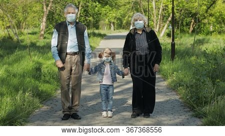 Old Grandparents With Granddaughter Together Walk In Spring Park In Medical Masks. Coronavirus Covid