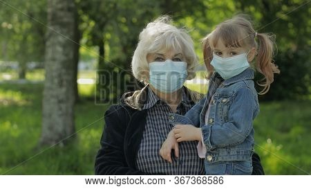 Old Grandmother With Granddaughter Together In Spring Park In Medical Masks. Coronavirus Covid-19 Pa