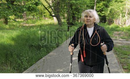 Active Senior Elderly 80 Years Old Caucasian Woman Training Nordic Walking With Ski Trekking Poles I