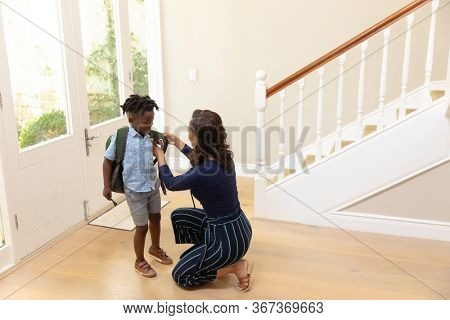 Side view of a mixed race woman at home, kneeling in the hallway by the front door, preparing and saying goodbye to her young son, before he leaves for school with his backpack on