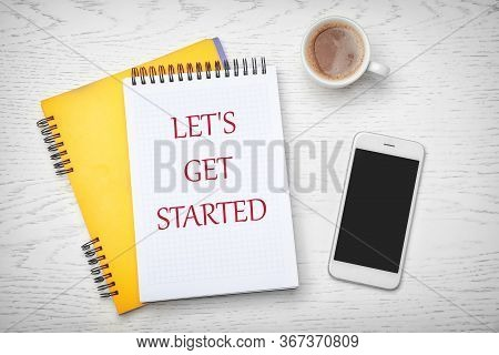 Notebook With Phrase Let's Get Started, Smartphone And Cup Of Coffee On White Wooden Background, Fla