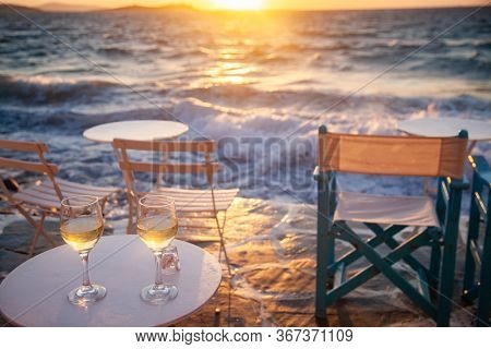 restaurant table by the sea with white wine at sunset summer holiday concept