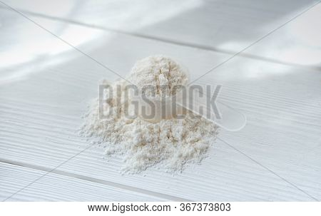Collagen Or Protein In Powder On White Wooden Table. Protein Powder For Making Whey Drink Or Collage