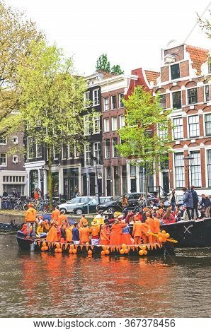 Amsterdam, Netherlands - April 27, 2019: Party Boats On Canal With People Dressed In National Orange