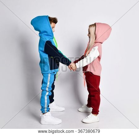 Little Kids, Brother And Sister, In Hoods, Colorful Tracksuits And Sneakers. They Holding Hands, Pos
