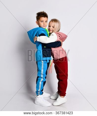Little Kids, Brother And Sister, In Hoods, Colorful Tracksuits And Sneakers. Elder Brother Hugging H