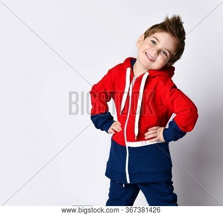 Little Blond Boy In Blue And Red Tracksuit. He Is Smiling, Put Hands On Hips, Posing Isolated On Whi
