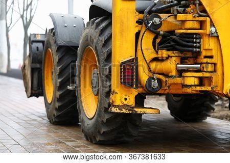 Excavator Standing At Pavement Ready To Work. Digger Is Equipped With Bucket. Main Purpose Is Develo