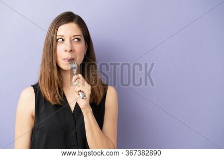 Cute Woman In Her 40s Eating Some Tasty Food With A Fork And Looking At Copy Space In A Studio