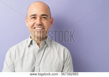 Closeup Of A Man In His 30s Looking Happy And Smiling In A Studio With Purple Background