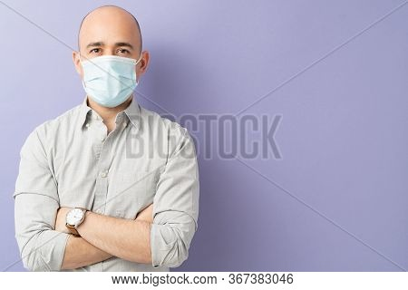 Man With Arms Crossed Wearing A Face Mask During Covid19 Pandemic With A Lot Of Copy Space
