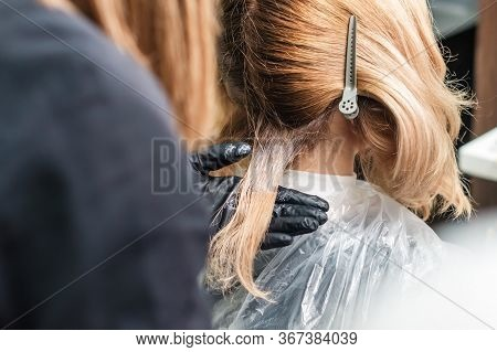 Hair Dyeing Of Young Woman By Hands Of Hairstylist Close Up.