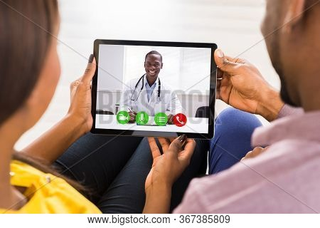 Pregnant Couple In Online Video Conference Call With Doctor