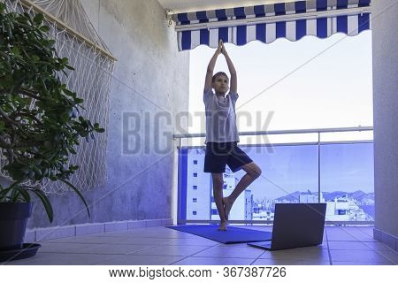 Boy Doing Sport Exercises, Practicing Yoga On Balcony. Sport, Healhty Lifestyle, Active Leisure At H