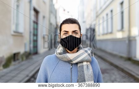 health, safety and pandemic concept - young woman wearing black face protective reusable barrier mask in city