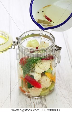 homemade pickles making process ; pouring with pickles brine