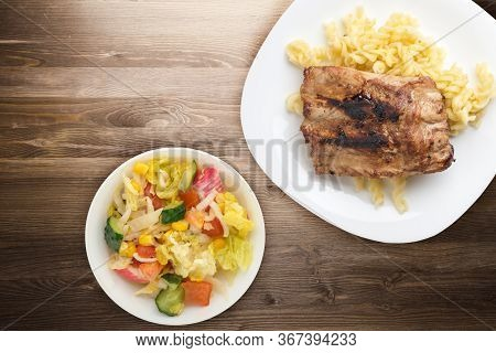 Grilled Pork Ribs With Pasta. Grilled Pork Ribs On A White Plate On A Brown Wooden Background. Grill