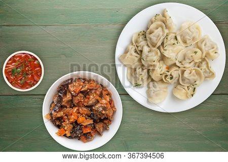 Dumplings On A White Plate On Green Wooden Background .boiled Dumplings With Salad.meat Dumplings To