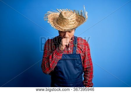 Young handsome chinese farmer man wearing apron and straw hat over blue background feeling unwell and coughing as symptom for cold or bronchitis. Health care concept.
