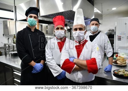 Mixed race team Portrait of group chefs standing together in the kitchen at restaurant wearing protective medical mask and gloves in coronavirus new normal concept