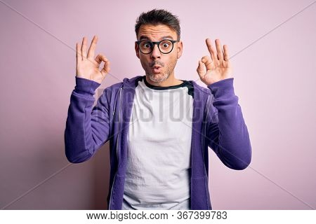 Young handsome man wearing purple sweatshirt and glasses standing over pink background looking surprised and shocked doing ok approval symbol with fingers. Crazy expression