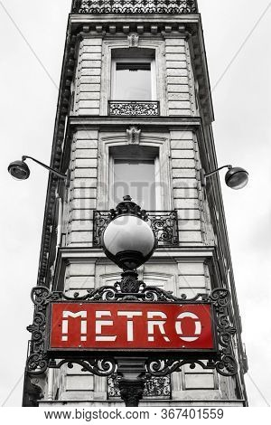 Retro style Parisian building  detail in black and white with traditional Art Deco Metro sign highlighted in red. Processed to look like an old photo with selective focus on Metro sign.