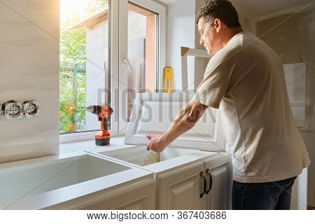 Middle-aged Caucasian Man Holds Kitchen Cabinet Door , Preparing For The Process Of Custom Installat