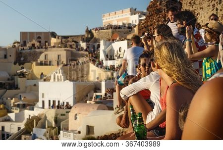 Oia, Santorini, Greece - 22 July 2014: Crowds Of Tourists Drinking, Photographing And Waiting For Su