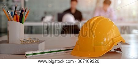 Close Up View Of Engineer Worktable With Safety Helmet, Glasses And Other Supplies On White Desk In