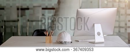 Close Up View Of Engineer Worktable With Computer, Safety Helmet, Stationery And Copy Space