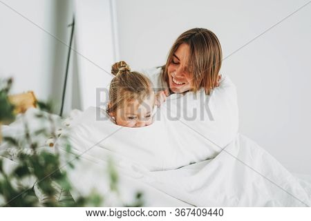 Cute Toddler Girl Long Fair Hair Big Grey Eyes Looking At Camera Having Fun With Mother On Bed Stay