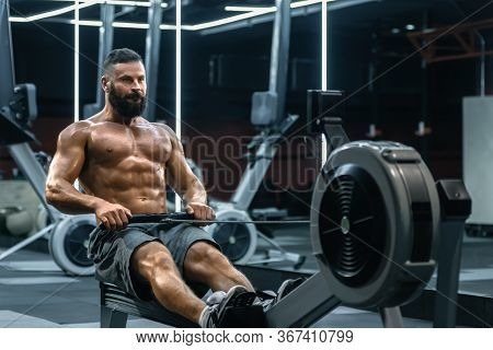 Young Strong Bearded Bodybuilder Doing Low Cable Pulley Row Seated