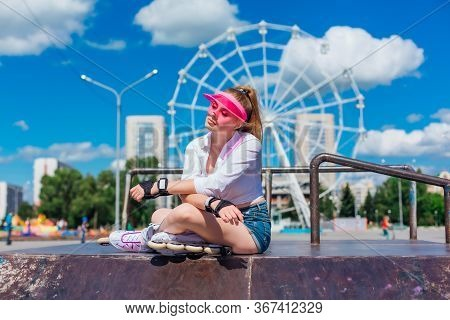 Portrait Of An Emotional Girl In A Pink Cap Visor Wearing Protective Gloves And Rollerblades Sitting