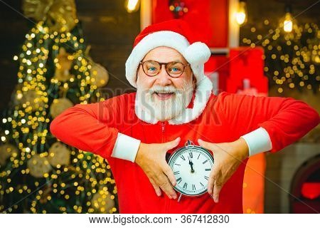 Thanksgiving Day And Christmas. Santa Claus Holding Alarm Clock Against Christmas Tree Background. N