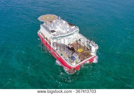Large Platform Supply Ship With Helipad And Two Large Cranes, Anchored At Sea.