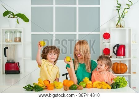 Mom Daughter And Son Prepare A Smoothie In The Kitchen. Have Fun And Play With Vegetables. Healthy D