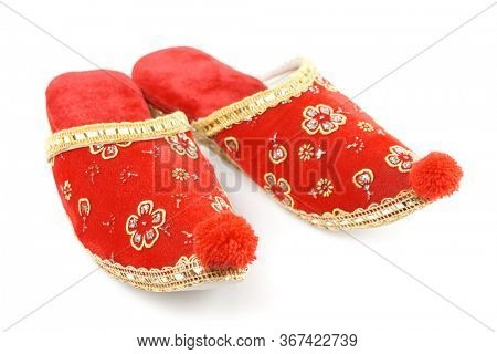 Red embroidered Turkish slippers, decorative footwear isolated on white background