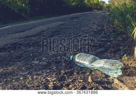 Plastic Bottle With Water By The Road. Environmental Pollution Concept.