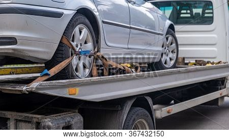 Loaded Broken Car On A Tow Truck. Car Being Towed. Damage Vehicle After Crash Accident