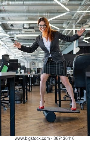 The Cheerful Business Woman In Red High Heels Catches Equilibrium On A Balance Board In Office. A Fe