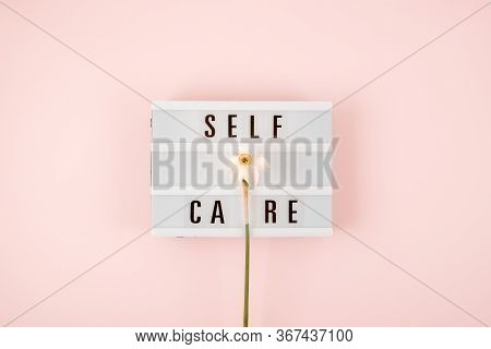 Self-care Word On Lightbox And Flower Narcissus On Pink Background Flat Lay. Take Care Of Yourself.