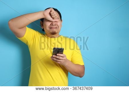 Attractive Young Asian Man Reading Texting Chatting  On His Phone, Bad News, Sad  Crying Expression