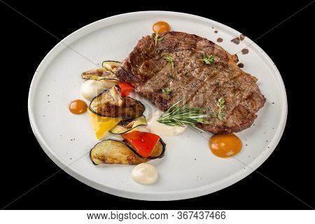 Grilled Beef Steak On A White Plate. Served With A Side Dish Of Vegetables. Isolated On A Black Back