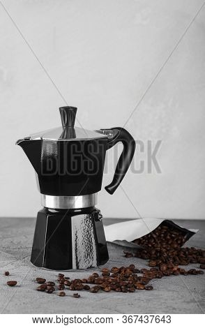Black Geyser Coffee Maker On A Stone Table. Coffee Beans Are Scattered Nearby.