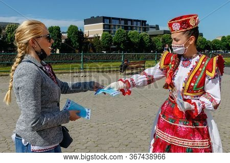 Uzhgorod, Ukraine - May 21, 2020. A Girl In Ukrainian National Costume Gives Passers-by Protective M