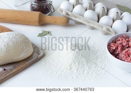 Flour Lies On The Table, Next To Minced Meat, Eggs, Dough. Dumplings, Russian Cuisine. Sculpt Buuzy,